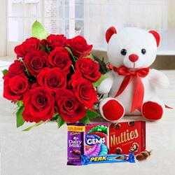 Fantabulous bouquet of 12 Red Roses, adorable Teddy with luscious mixed Cadburys Chocolate  to Baraut