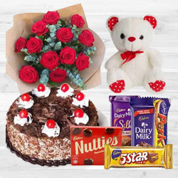 Creative Bouquet of 12 Dutch Red Roses with 1 Lb Cake, Mixed Cadburys Chocolates and a Teddy Bear to India