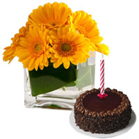 Mouth-watering Chocolate Cake with Candles and Gerberas in a vase for Midnight Delivery to Hyderabad