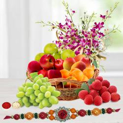 Tropical Fresh Fruits Basket decorated with Orchids with 1 Regular Rakhi and Roli Tilak Chawal to Ludhiana