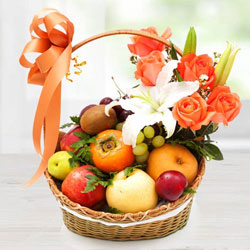 Decorative Imported Fruits Basket with Orange Roses n White Lily to Alwar